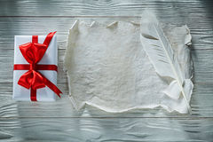 Plume il contenitore di regalo avvolto strato di carta d'annata sul bordo di legno fotografia stock