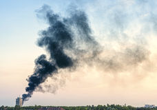 Plume of smoke from a fire above city at sunset Royalty Free Stock Photography