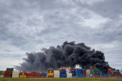 A plume of toxic smoke at a West Footscray factory fire as seen from behind shipping containers. Melbourne, Victoria, Australia 30 royalty free stock image