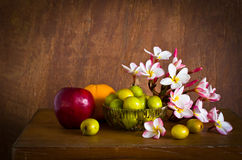 Plumeria flower and many fruit on old wood table Royalty Free Stock Images