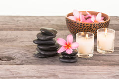 Plumeria flowers, black stones and candles. On wooden table close up Royalty Free Stock Photos