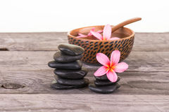 Plumeria flowers and black stones on weathered wood Royalty Free Stock Photos