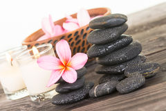 Plumeria flowers and black stones on weathered wood close up Royalty Free Stock Photos