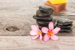 Plumeria flowers, soaps and black stones close-up Royalty Free Stock Photos