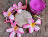 Plumeria (Frangipani) flowers, Purple candles in glass and spa stone on wooden background. Royalty Free Stock Photos