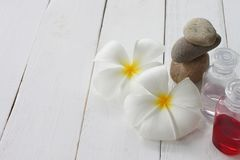 Plumeria and Gel bottle is placed on a white wooden floor stock photos