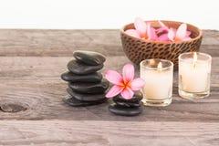 Plumeriablumen, schwarze Steine und Kerzen Lizenzfreie Stockfotos