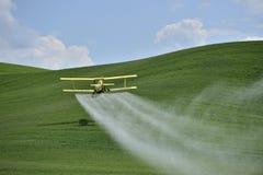 Plumero de la cosecha del biplano que pinta (con vaporizador) un campo de granja. Imágenes de archivo libres de regalías