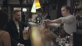 Plump bartender pouring alcohol in the glass using measuring cup and giving it to the client. The young bearded man and. The young bearded man and unrecognizable stock footage
