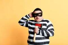 Plump criminal wearing mask scratching his head , holding ax. In hand  yellow background. studio shot stock image