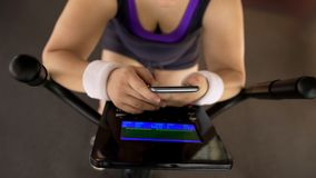 Plump female riding stationary bike, viewing fitness application on smartphone royalty free stock photography