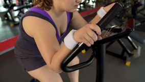 Plump female working stationary bike in sports club, body fitness stock photography