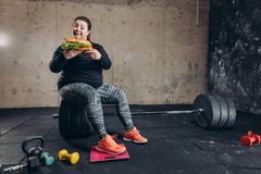 Plump girl with bad habit. Copy space. stolen pleasures are sweet. woman pretends that she leads healthy lifestyle. unhealthy diet royalty free stock images