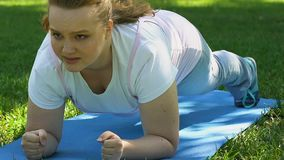 Plump girl doing plank outdoor, endurance and strength, healthy lifestyle. Stock footage stock video