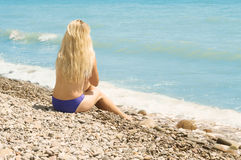 Plump girl sitting on the sea beach. Rear view Stock Photography