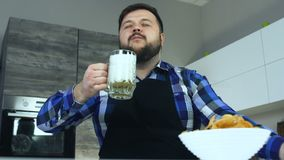 Fat man sits in the kitchen at the table and drinks foamy beer from mug. A thick guy in an apron sitting at the table. Plump guy with beard in apron pours beer stock video