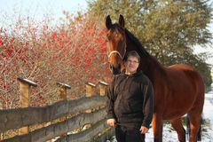 Plump happy teenager boy and brown horse portrait Stock Images