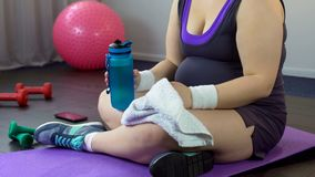 Plump lady drinking water and restoring breath after exhausting home workout royalty free stock photography
