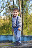 Plump little boy with bow tie and jeans grimaces Royalty Free Stock Images