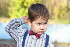 Plump little boy in shirt and bow tie thinks Stock Photography