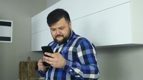 Plump man with beard stare at phone and flips. Fat guy swipe a phone display. Male with a cup of coffee looks news feed. Fat bearded man in shirt with a cup of stock footage