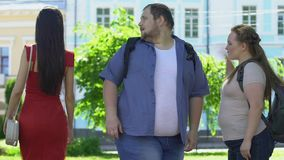 Plump man looking at lady in red dress, obese girlfriend jealous, relationship. Stock footage stock video