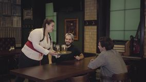 Plump waitress with pigtails in white blouse and corset bringing cold beer to the men sitting at the table in the bar. Leisure in the modern cafe stock video footage