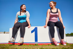 Plump winners. Two happy plump women sharing first place on podium Stock Photo