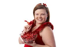 Plump woman with Christmas fondant smiling. Plump woman in red with a bowl of Christmas fondant, smiling stock photography