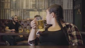 Plump woman with pigtails sitting at the bar counter with a glass of beer while two men drinking alcohol in the. Background. Men and woman looking at each other stock footage