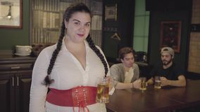 Plump woman with pigtails in white blouse and corset holding beer glass looking towards two men drinking alcohol in the. Background. Leisure at the bar stock footage