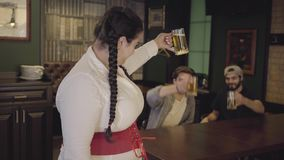Plump woman with pigtails in white blouse and corset raising glass of beer looking towards two men drinking alcohol in. Plump woman with pigtails in white blouse stock video footage