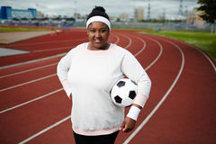 Plump woman posing with soccer ball at track and field stadium stock photo
