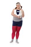 Plump woman with scale. Plump woman in sportswear holding a scale in hands, looking away stock image