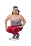 Plump woman squatting on scale disappointed Stock Image