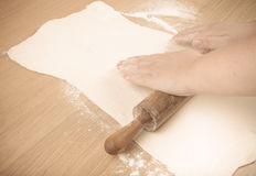 Plump women's hands roll out the dough on a light wooden table. Royalty Free Stock Images