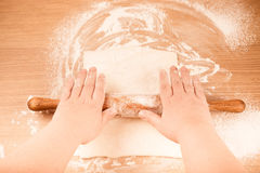 Plump women's hands roll out the dough on a light wooden table. Stock Photo