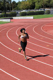Plump young black woman running on track Royalty Free Stock Image