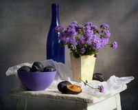 Plums. Nice still life with plums and flowers Ageratum Stock Images