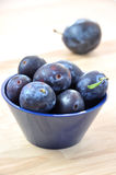 Plums. Fresh ripe plums in a navy blue bowl on wooden table Stock Photography