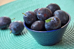 Plums. Fresh plums in a bowl in turquoise mat Royalty Free Stock Photos
