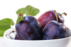 Plums. In bowl and green leaves in the background Stock Photos