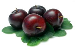 Plums. Four Black Plums with leaves, isolated on white royalty free stock photos