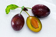 Plums. Delicious two and a half plums on a white with water drops Royalty Free Stock Photos