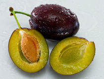 Plums. Delicious one and a half plums on a white with water drops Royalty Free Stock Photos