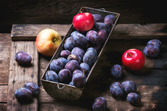 Plums and apples. Vintage metal bowl with plums and apples over old wooden table. See sries stock photo