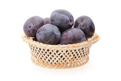Plums in basket. On white background Stock Photography