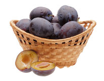 Plums in basket and cut plum. On white background Stock Photo