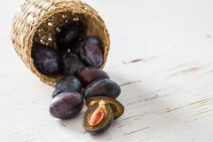 Plums in basket, white wood background. Copy space Stock Photography