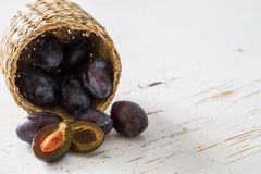Plums in basket, white wood background. Copy space Royalty Free Stock Photography